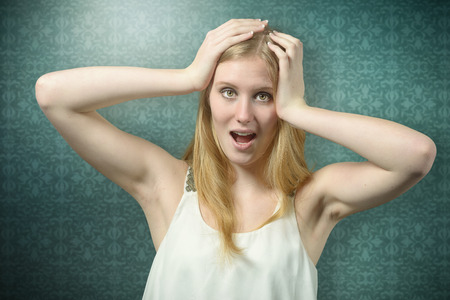 astounded: Close up Shocked Woman with Blond Hair Holding her Head While Looking at Camera, on green background