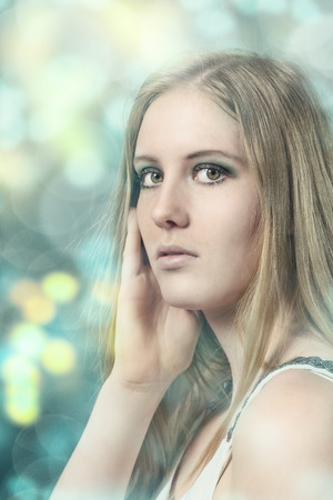 tourquoise: Close up Portrait of Pretty Young Blond Woman with her hand to her face While Looking at the Camera on Abstract Glowing Background.