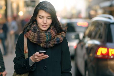 vrouwen: Modieuze jonge vrouw in zwarte jas en kleurrijke sjaal Druk bezig met haar mobiele telefoon tijdens het lopen een stad straat