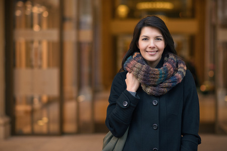 Stylish Pretty Young Woman in Autumn Fashion walking in the city, Looking at the Camera.