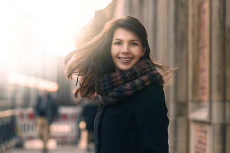 Happy woman with a lovely smile standing in her coat and scarf on an urban street in winter looking at the camera with a joyful expression and her hair blowing in the wind Фото со стока