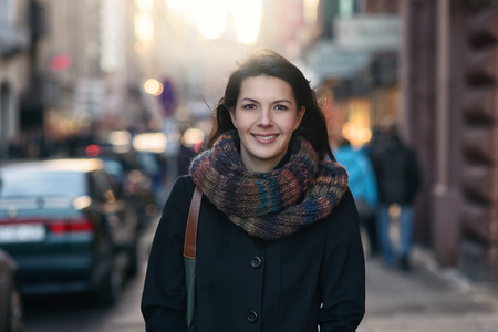 秋のファッションは都市圏内でスタイリッシュなのはかなり若い女性の肖像画、カメラ目線します。 写真素材