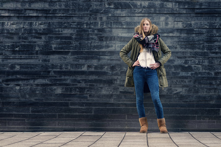 Fashionable Young Woman in Winter Outfit Posing in Front Old Gray Wall while Looking at the Camera. Stock Photo
