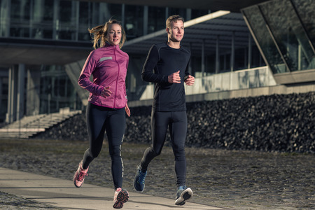 evening: Active young couple jogging side by side in an urban street during their daily workout in a health and fitness concept Stock Photo