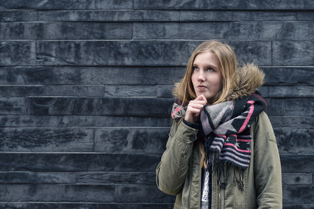 forgetful: Thoughtful pretty blond girl standing in front of a textured grey brick wall with her hand to her chin staring pensively up into the air with copy space Stock Photo