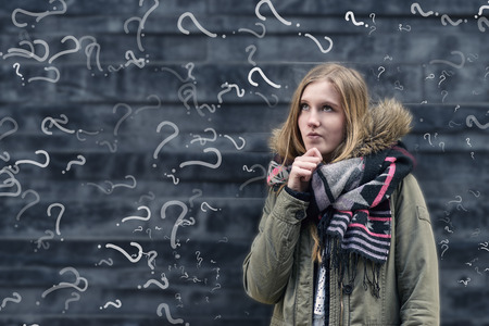 Pretty young female student in class with a problem to solve standing in front of a chalkboard in class covered in question marks looking thoughtfully into the air with her hand to her chin Foto de archivo