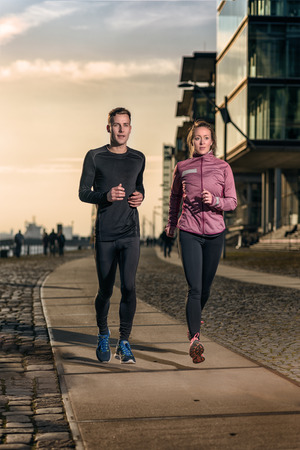 Active young couple jogging side by side on a harbor promenade at sunset during their daily workout in a health and fitness concept Standard-Bild