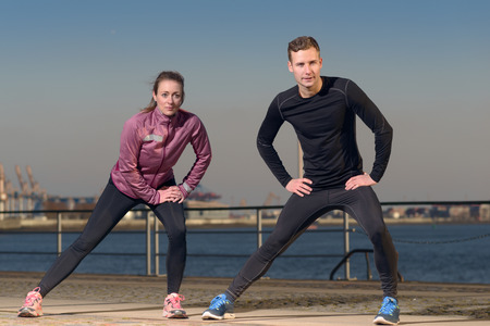 limbering: Young couple exercising at the waterfront standing on the esplanade in front of the harbor warming up their muscles doing stretching exercises before doing a workout or going jogging