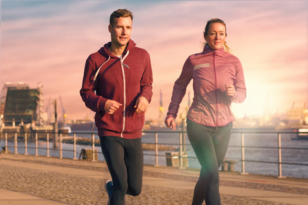 Fit actieve jonge paar draaien op een boulevard met de atletische vrouw leidt de weg naderen van de camera in een gezonde lifestyle concept Stockfoto