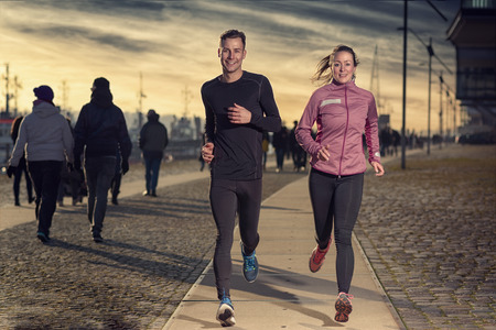 physical activity: Active young couple jogging side by side on a harbor promenade at sunset during their daily workout in a health and fitness concept Stock Photo