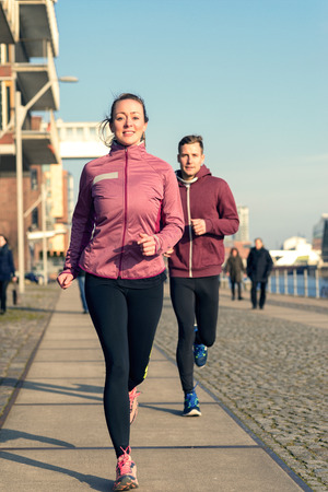 leading the way: Fit active young couple running on a seafront promenade with the athletic woman leading the way approaching the camera in a healthy lifestyle concept