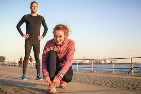 bending down: Sporty active couple on a seafront promenade getting ready to go for a jog in their daily workout with the attractive young woman bending down to tie her laces on her trainers with a smile Stock Photo