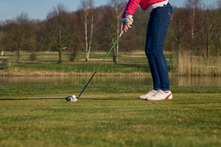 lower body: Close up low angle view of the lower body of a woman teeing off at a golf course with a driver Stock Photo