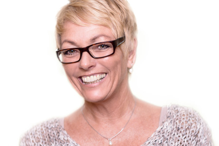 attractive charismatic: Head and shoulders portrait of a happy attractive middle-aged blond woman wearing glasses looking at the camera with a lovely vivacious smile