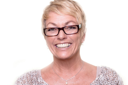 Head and shoulders portrait of a happy attractive middle-aged blond woman wearing glasses looking at the camera with a lovely vivacious smile