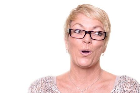 Aantrekkelijke blonde vrouw draagt een bril middelbare leeftijd zien waarderend verwondering of verbazing zeggen Ooh met een geamuseerde blik terwijl zijwaarts blik Stockfoto