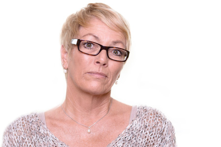 실내 창 유리 창에 대 한 카메라, 머리와 어깨에 열심히 찾고 심각한 단 발 렌더링 식과 안경을 착용하는 불신 한 스턴 중 년 여자
