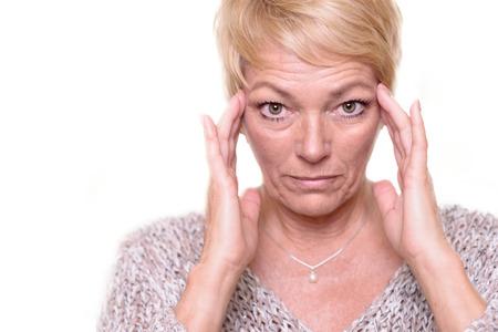 Aantrekkelijke senior blonde vrouw met een grote ogen expressie en haar bril op haar hoofd die haar teint als ze eruit ziet in de spiegel Stockfoto