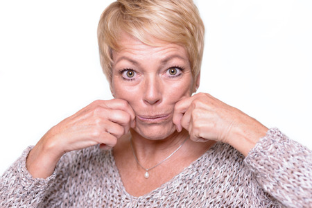 aging face: Attractive middle-aged woman with short blond hair trying to reverse the signs of aging by pulling on her cheeks with her hands to give herself a temporary face lift