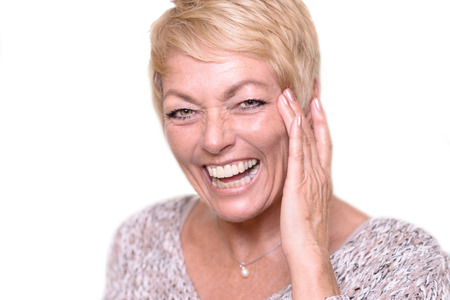 クローズ アップ幸せな中年女、短いブロンドの髪、笑っている間に触れる彼女の顔とカメラを見てみる。