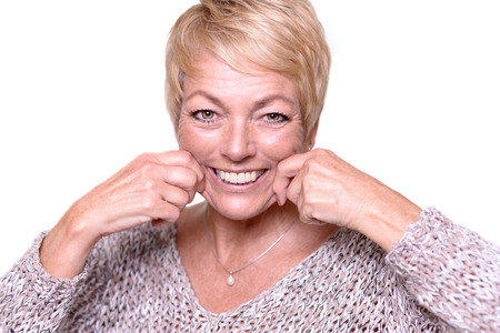 Attractive middle-aged woman with short blond hair trying to reverse the signs of aging by pulling on her cheeks with her hands to give herself a temporary face lift
