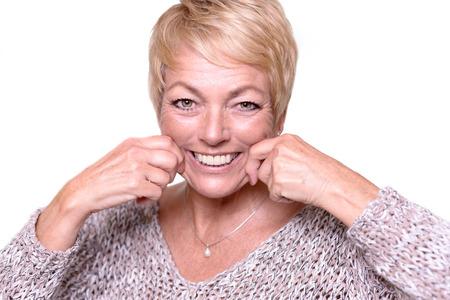 Aantrekkelijke vrouw van middelbare leeftijd met kort blond haar proberen om de tekenen van veroudering te keren door te trekken op haar wangen met haar handen om zichzelf een tijdelijke face lift geven Stockfoto