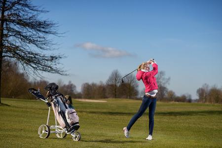 teen golf: Atractivo delgado joven golfista que juega un golpe de aproximación en la calle observando el vuelo de su bola después de la carrera con su bolsa de golf detrás de ella
