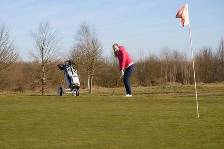 teen golf: Hembra Joven golfista en un campo de entrenamiento deportivo, el uso de chaqueta y los pantalones vaqueros, picar la pelota de golf en la Copa con la bandera Foto de archivo