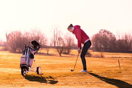 teen golf: Mujer golfista jugando una ronda de golf a finales de la luz del sol por la noche haciendo cola en la calle para un tiro con su carrito de golf en el primer plano y largas sombras proyectadas por el sol
