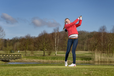 follow through: Woman golfer hitting a golf ball on the fairway with a club standing in the follow through position after the stroke in front of a pond or water hazard on a rural golf course