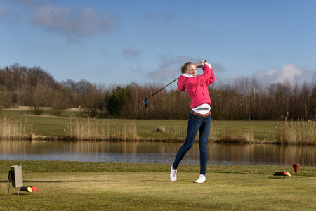 Woman golfer hitting a golf ball on the fairway with a club standing in the follow through position after the stroke in front of a pond or water hazard on a rural golf course