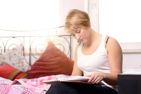 shining through: Pretty young female student reading in a textbook while sitting in her bedroom, the sun shining through the window