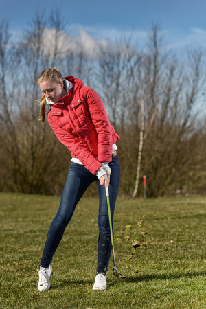 skinny jeans: Full Length Shot of a Young Female Golfer, Wearing Red Jacket and Skinny Jeans, in the Rough, just having played a ball Stock Photo