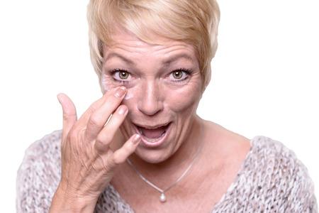 Middelbare leeftijd aantrekkelijke blonde vrouw toepassing van anti-aging crème om de rimpels rond haar ogen in een poging om de bestrijding van veroudering in een huidverzorging en schoonheid concept Stockfoto