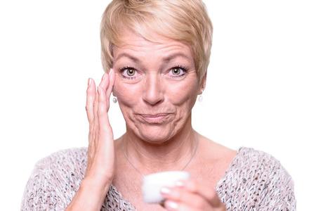 arrugas: Atractiva mujer rubia de mediana edad de aplicar la crema anti-envejecimiento para las arrugas alrededor de los ojos, en un esfuerzo para combatir el envejecimiento en un concepto de cuidado de la piel y la belleza Foto de archivo
