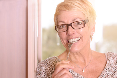 Close up Happy Middle Age Blond Woman, Wearing Eyeglasses, Biting a Fork While Looking at the Camera. Standard-Bild