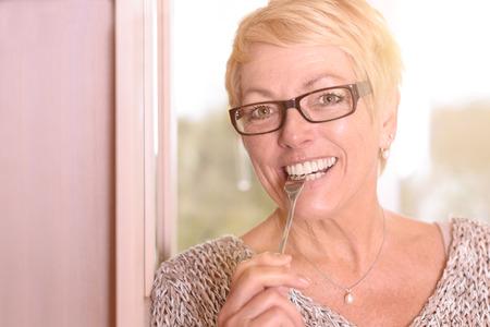 Close up Glückliche Mittelalter blonde Frau, Brille tragen, Beißen einer Gabel, während man die Kamera.