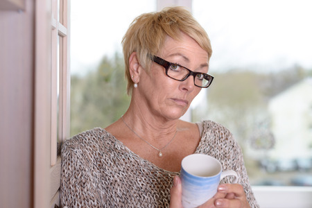 quizzical: Close up Serious Middle Age Woman Wearing Eyeglasses, with Short Blond Hair, Holding a Cup While Leaning on the Wall and Looking at the Camera. Stock Photo