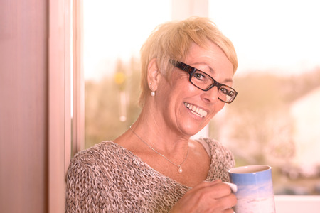 beaming: Vivacious attractive blond middle-aged woman wearing glasses standing drinking coffee and glancing sideways at the camera with a beaming smile