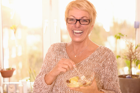beaming: Vivacious attractive middle-aged woman wearing glasses eating a healthy bowl of fruit salad rich in vitamins looking at the camera with a beaming friendly smile full of vitality