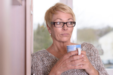 observant: Close up Serious Middle Age Woman Wearing Eyeglasses, with Short Blond Hair, Holding a Cup While Leaning on the Wall and Looking at the Camera. Stock Photo
