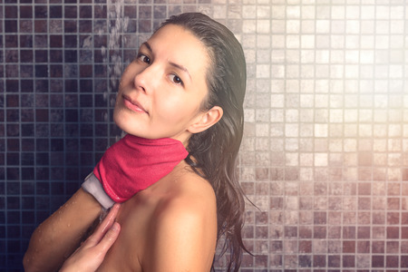 exfoliate: Close up Bare Pretty Woman Taking Shower at the Bathroom with Red Hand Glove, Looking at the Camera Stock Photo