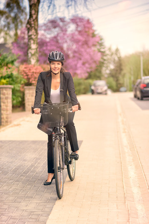 head gear: Happy Young Businesswoman Biking at the Street with Head Gear Going to her Office, Looking at the Camera