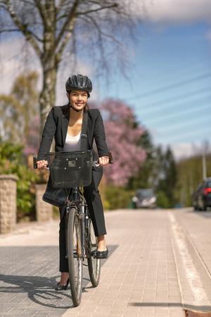 Happy jonge zakenvrouw Fietsen op de straat met HoofdToestel gaan naar haar kantoor, kijkend naar de camera