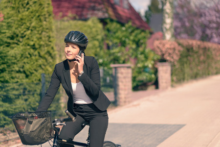slack: Active Young Businesswoman Riding on her Bicycle While Talking on her Mobile Phone.