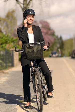 answer phone: Stylish friendly young businesswoman riding to work pausing to answer a call on her mobile phone standing supporting her bicycle in the road as she chats to her friend Stock Photo