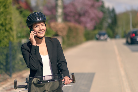 chats: Stylish friendly young businesswoman riding to work pausing to answer a call on her mobile phone standing supporting her bicycle in the road as she chats to her friend Stock Photo