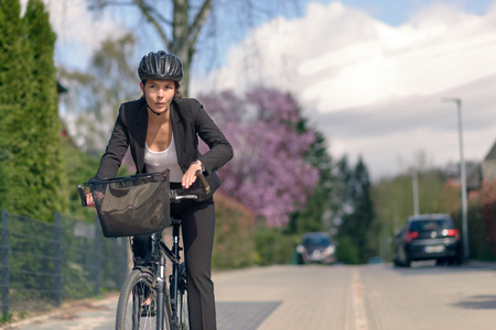 Young Active Businesswoman Commuting on a Bicycle with Protective Helmet Going to her Office photo