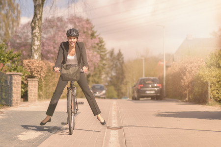 Stylish woman in a slack suit and safety helmet having fun riding to work on her bicycle lifting her feet in the air and balancing as she coasts along a residential road with a happy smile