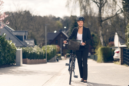 slack: Happy Young Businesswoman standing on the Street with her bike ready to go to the office, Looking at the Camera